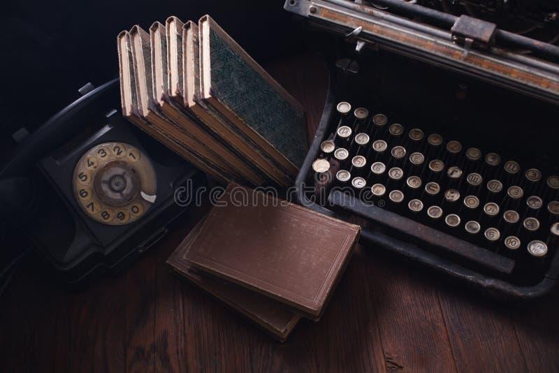 Teléfono retro viejo con la máquina de escribir y los libros del vintage en el tablero de madera fotografía de archivo libre de regalías