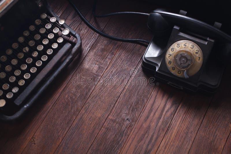 Teléfono retro viejo con la máquina de escribir y los libros del vintage en el tablero de madera fotos de archivo libres de regalías