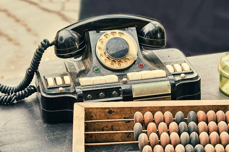 Teléfono retro viejo de la antigüedad de los objetos, ábaco que considera en la tabla de madera imagenes de archivo
