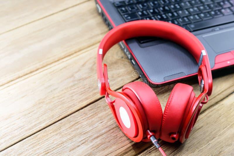 Teléfono rojo colocado en el portátil negro y en la mesa de madera fotografía de archivo