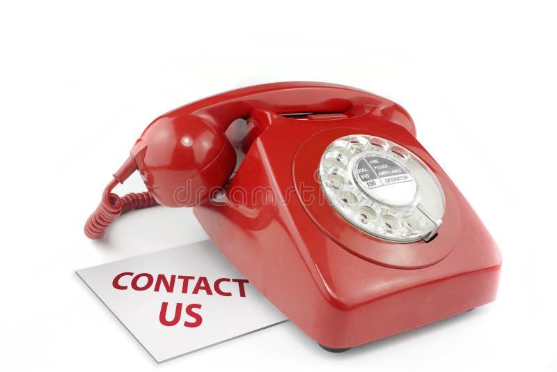 Teléfono rojo pasado de moda con el contacto nosotros messag fotografía de archivo