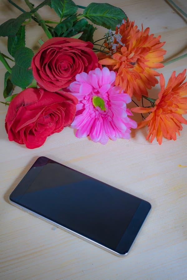 Teléfono, rosas rojas, Gerbera rosado hermoso imágenes de archivo libres de regalías