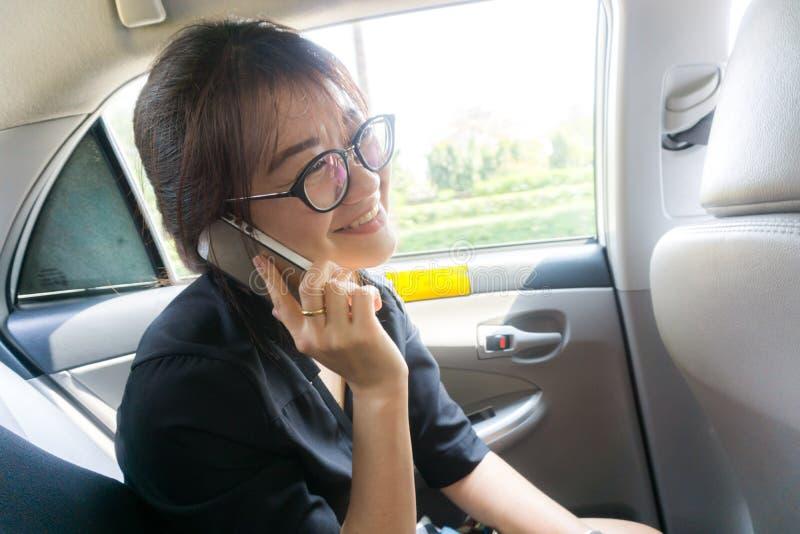 Teléfono taiking de la mujer asiática hermosa del negocio mientras que impuesto del pasajero imágenes de archivo libres de regalías