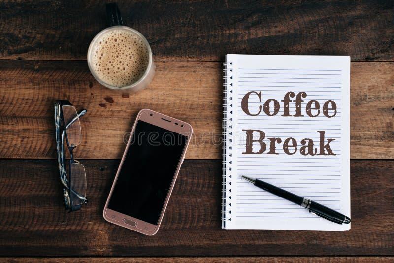 Teléfono, vidrios, taza del coffe y cuaderno con palabra del DESCANSO PARA TOMAR CAFÉ en la tabla de madera foto de archivo libre de regalías