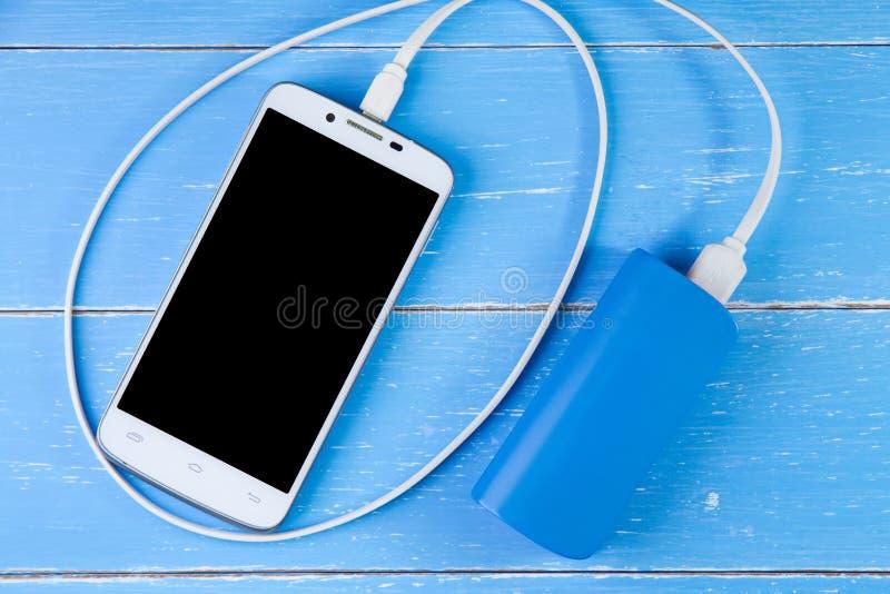 Teléfono y batería elegantes de la copia de seguridad en el fondo de madera azul imagen de archivo libre de regalías