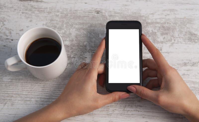 Teléfono y café de la mano en fondo de madera foto de archivo