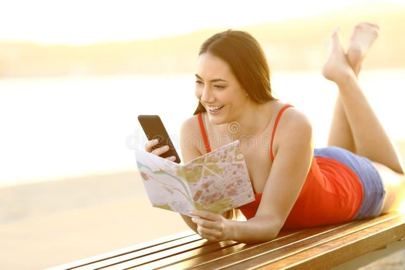 Teléfono y guía de comprobación turísticos felices en la playa fotos de archivo libres de regalías