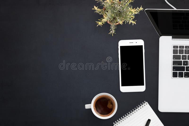 Teléfono y ordenador portátil elegantes en el escritorio de oficina negro con el espacio de la copia en lado izquierdo imagen de archivo