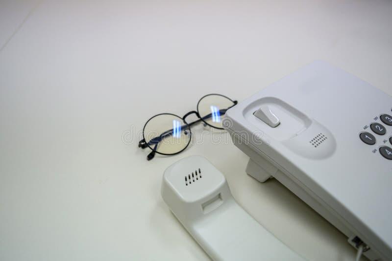 Teléfono y vidrio en el escritorio de oficina fotos de archivo