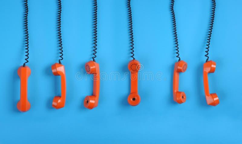 Teléfonos anaranjados sobre fondo azul imagen de archivo