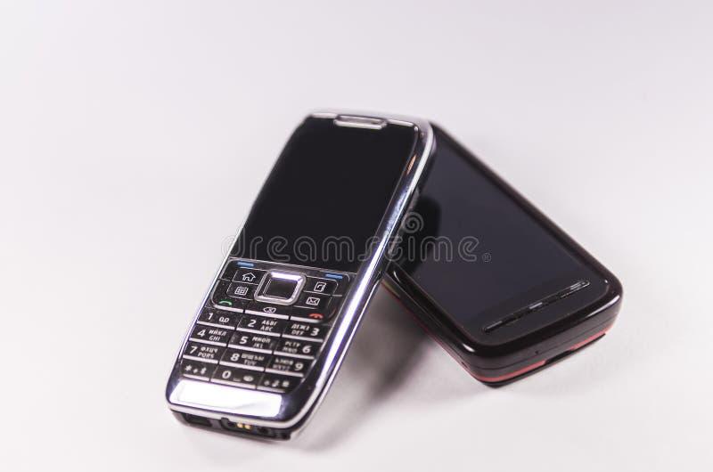 Teléfonos celulares pasados de moda aislados en el fondo blanco imagen de archivo libre de regalías