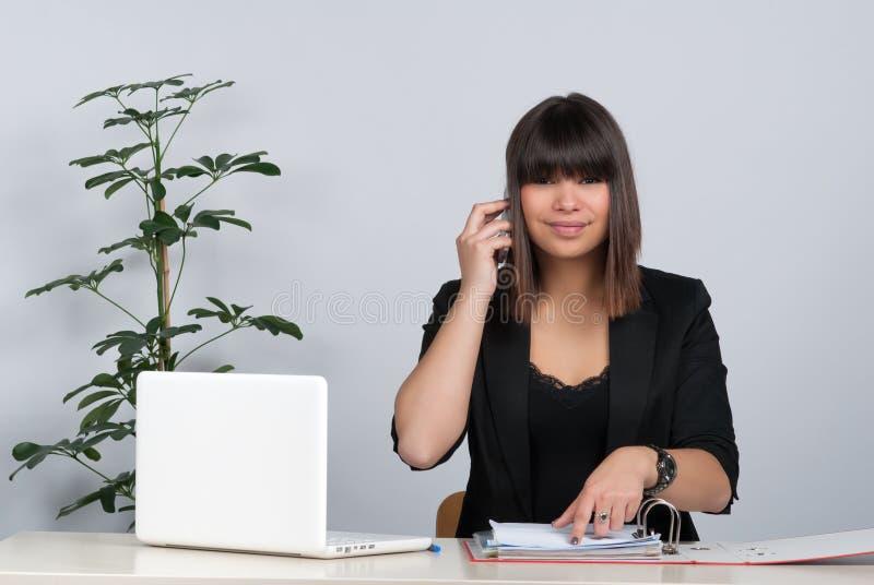 Teléfonos de la mujer en el escritorio foto de archivo libre de regalías