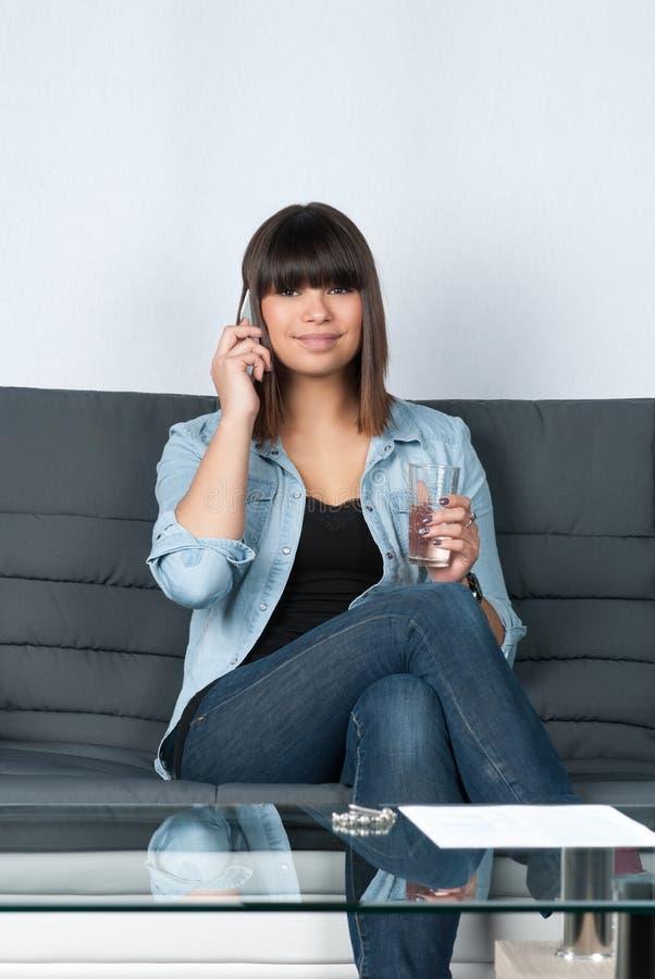 Teléfonos de la mujer en el sofá fotos de archivo