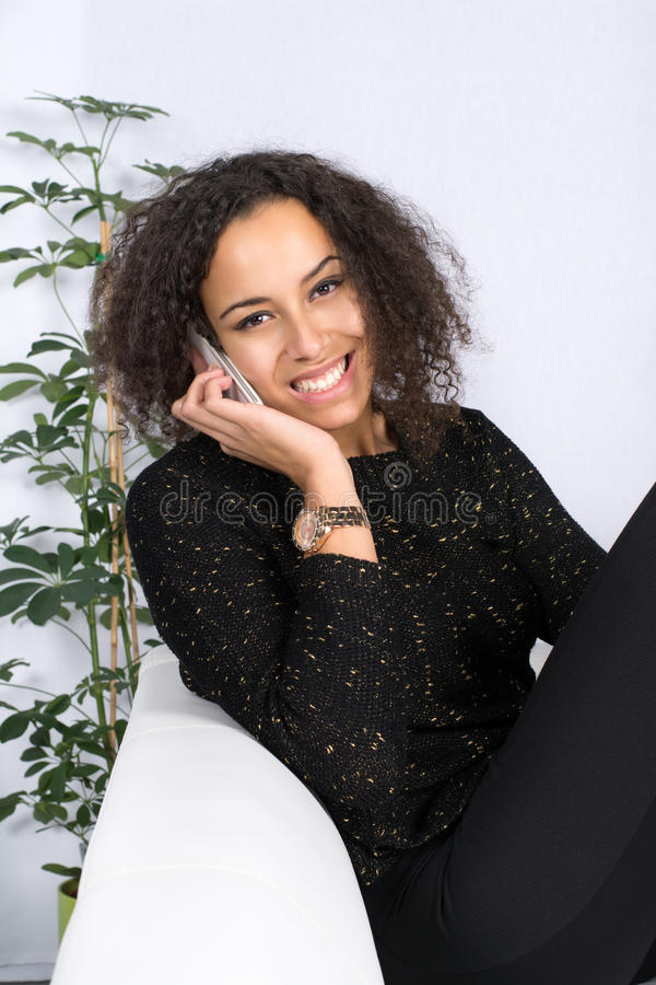 Teléfonos de la mujer joven imagen de archivo