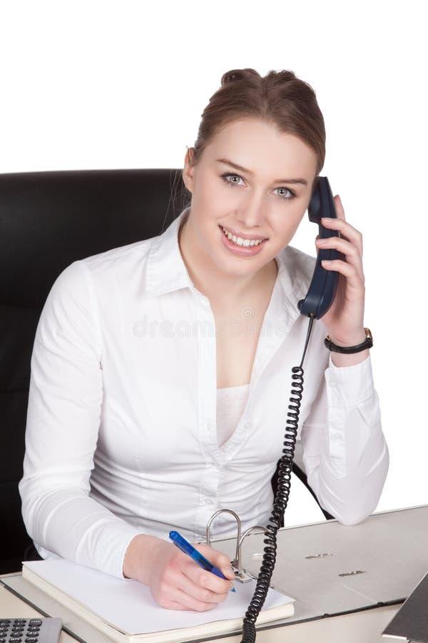 Teléfonos de la mujer joven en el escritorio fotos de archivo