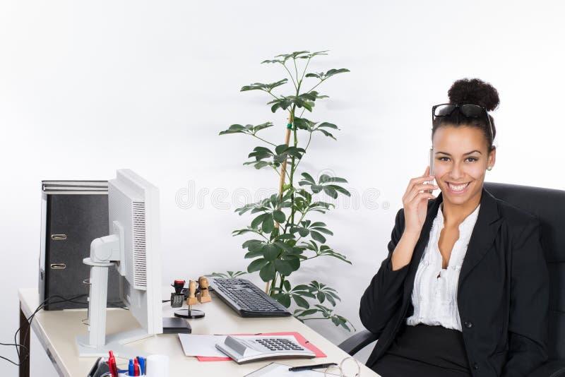 Teléfonos jovenes de la mujer de negocios en el escritorio fotos de archivo libres de regalías