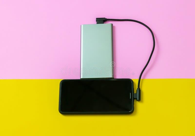 Teléfonos móviles de Smartphone que cargan las baterías por el banco del poder fotos de archivo libres de regalías