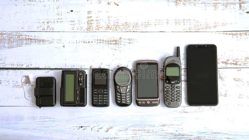 Teléfonos móviles viejos y paginadores aislados en el fondo de madera blanco imagenes de archivo