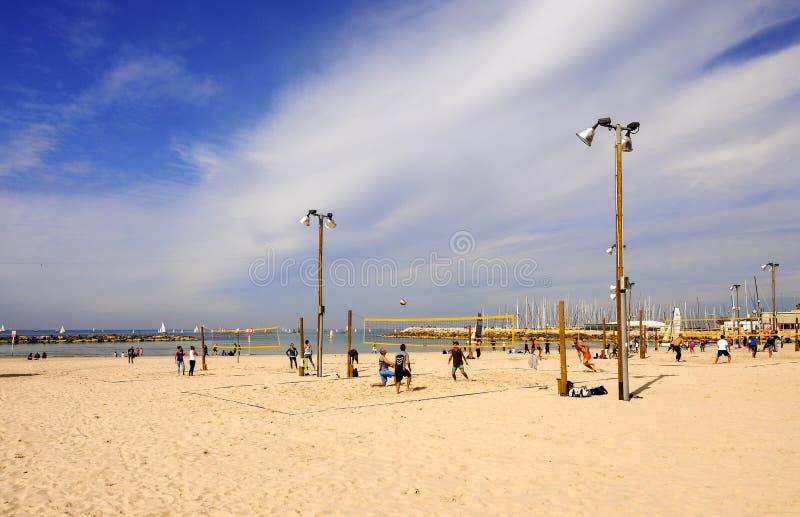 Tel Aviv, Israel - 4 de fevereiro de 2017: Grupo de jovens que jogam o voleibol no telefone Baruch da praia fotografia de stock