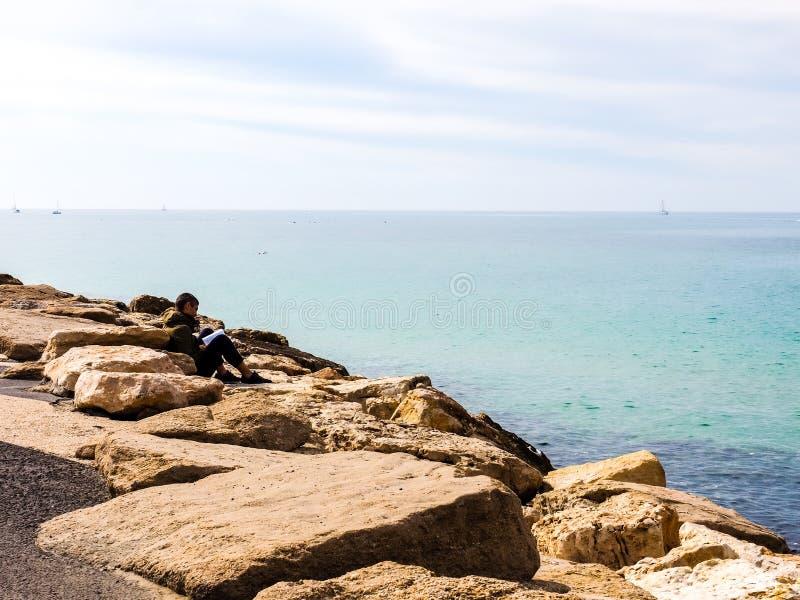 Tel Aviv, Israel - 4 de fevereiro de 2017: Homem que descansa e que lê um livro no telefone Baruch da praia fotos de stock royalty free