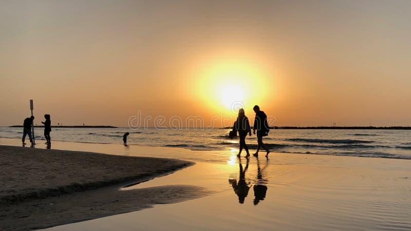 Tel-aviv, Israel - March 2018: People walking along Jerusalem Beach at sunset in Tel-aviv, Israel royalty free stock images