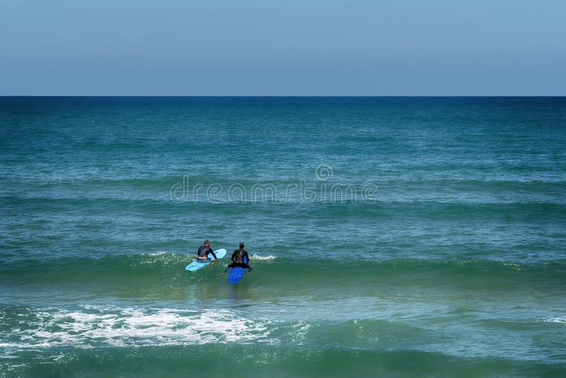 Tel-Aviv Israel May 19, 2019 View of the beautiful turquoise sea of Tel-Aviv, where two surfers float on their board in the waves. stock images