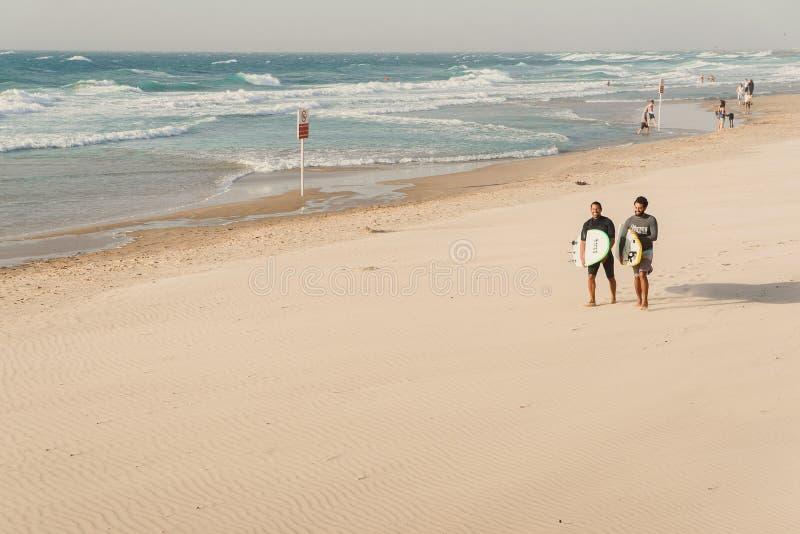 Tel Aviv, Israel - 3. November 2018: Zwei junge Surfer mit Surfbrettern geht den sandigen Strand des Mittelmeeres lizenzfreies stockfoto