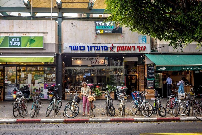 Tel Aviv, Israel - 26. Oktober 2018 - ein Tel Aviv-Bewohner, der Ihr Fahrrad vor einem lokalen Einzelhändler in im Stadtzentrum g stockfotos