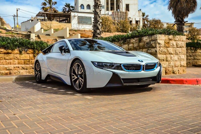 Tel Aviv, Israel - 15 02 2018: Weißes BMWs i8 Parkplatz auf der Straße nahe weißem Haus und Palmen Luxushybridfahrzeug lizenzfreie stockfotos