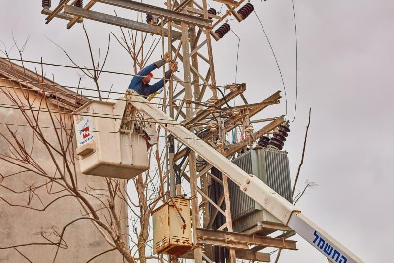 Tel Aviv - 10 06 2017: Naprawa mężczyzna załatwia elektryczną linię w Tel zdjęcia stock