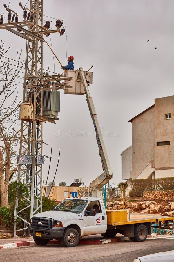 Tel Aviv - 10 06 2017 : Répare l'homme fixant la ligne électrique dans le téléphone photo libre de droits