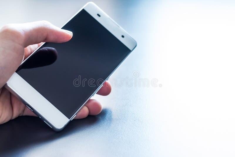 Tel?fono elegante moderno en la mano imagenes de archivo