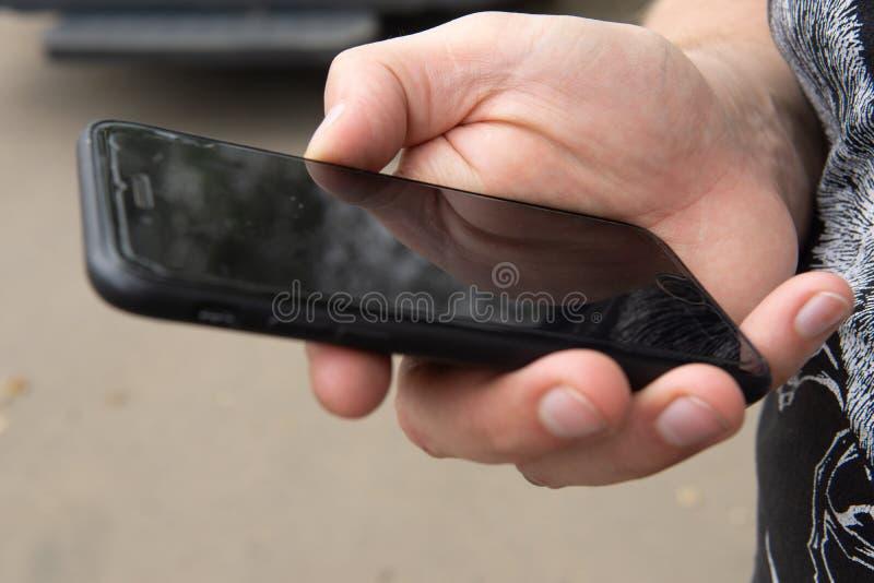 Tel?fono m?vil negro en la mano masculina fotos de archivo