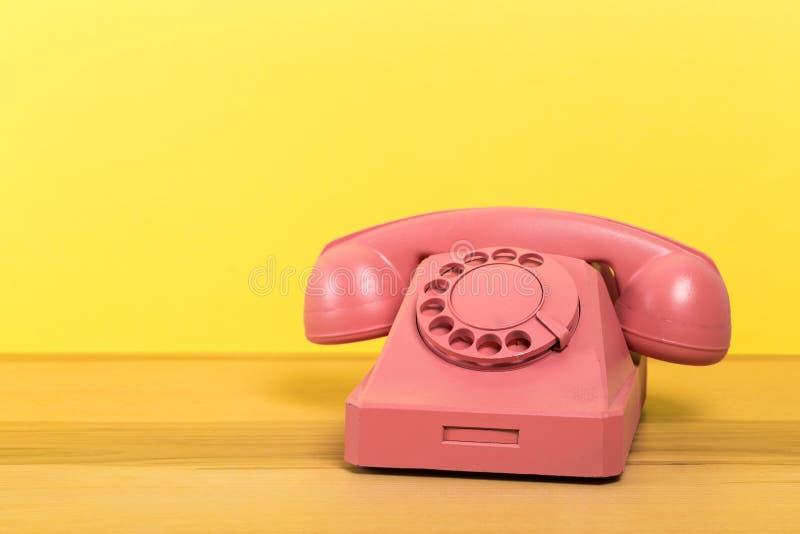 Tel?fono rosado del vintage en la tabla de madera con el fondo de la pared del color fotos de archivo
