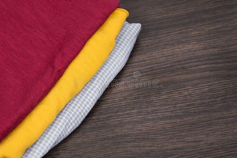 Tela amarilla y roja una pila de ropa, y de materias textiles Muestras de tela del color en la tienda Tela a cuadros gris calient fotos de archivo