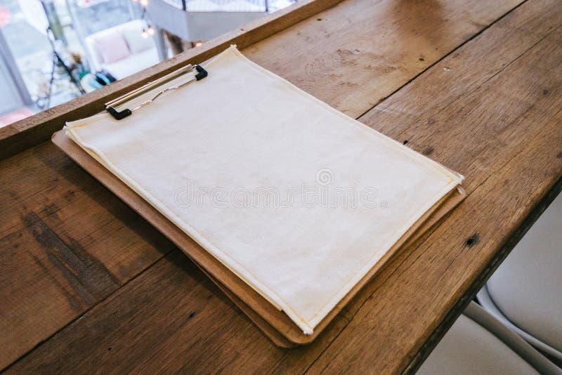 Tela blanca en blanco en lugar del tablero de papel en la tabla superior de madera imagen de archivo