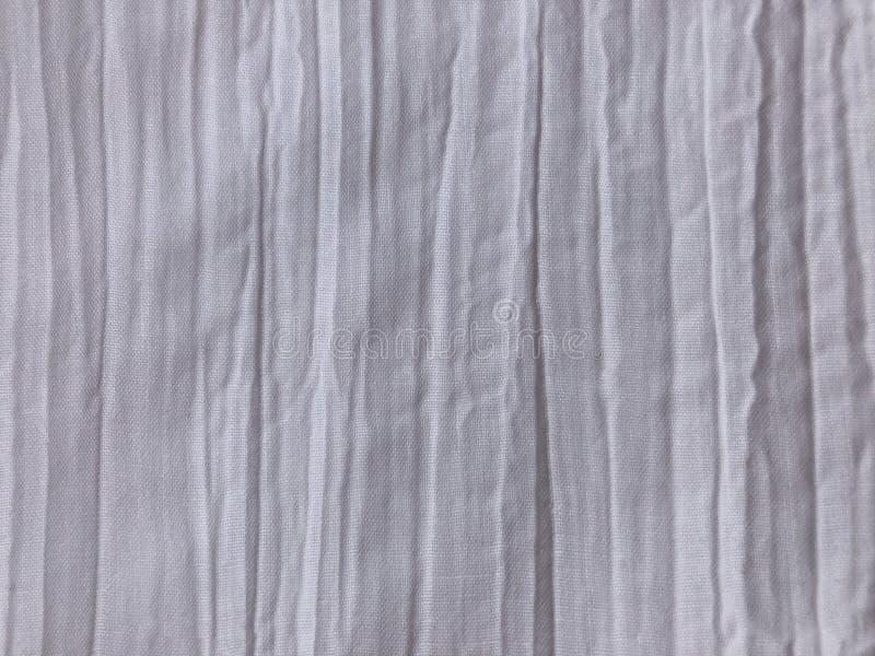 Tela branca com um efeito amarrotado e uns vincos verticais foto de stock