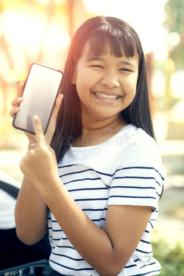 Tela branca da mostra asiática do adolescente da tela esperta do telefone e da emoção de sorriso toothy da felicidade da cara fotos de stock royalty free