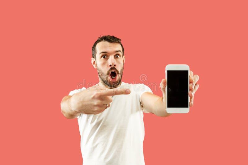 Tela considerável nova do smartphone da exibição do homem isolada no fundo coral em choque com uma cara da surpresa imagem de stock