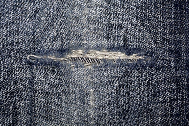 Tela das calças de brim com fissura imagens de stock