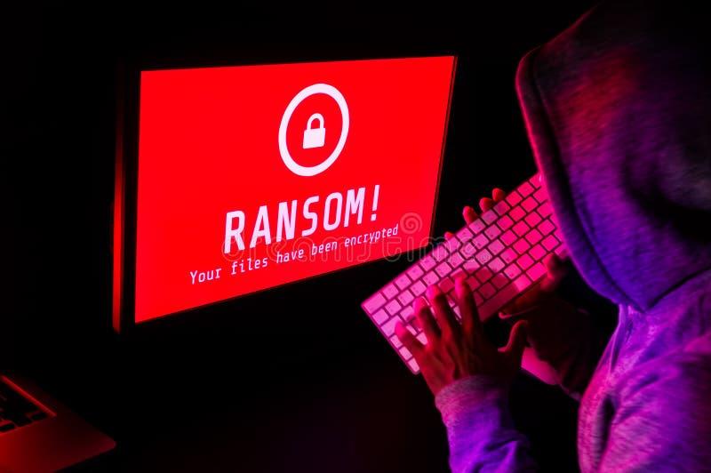 Tela de computador com alerta do ataque do ransomware no vermelho e em um hacker imagens de stock