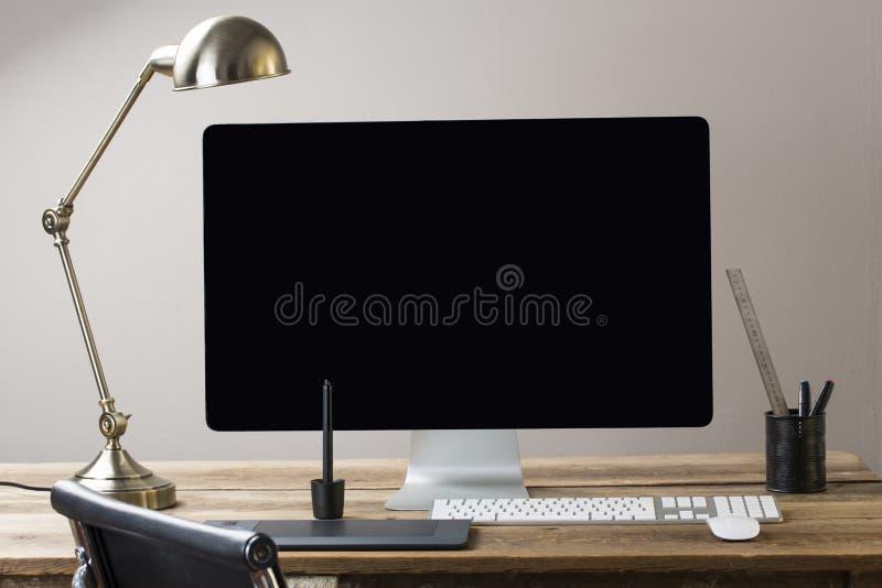Tela de computador e teclado e rato em uma tabela de madeira com whit
