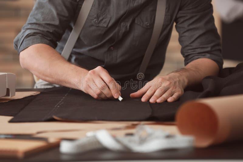 Tela de marcado del sastre joven con tiza en taller imagen de archivo libre de regalías