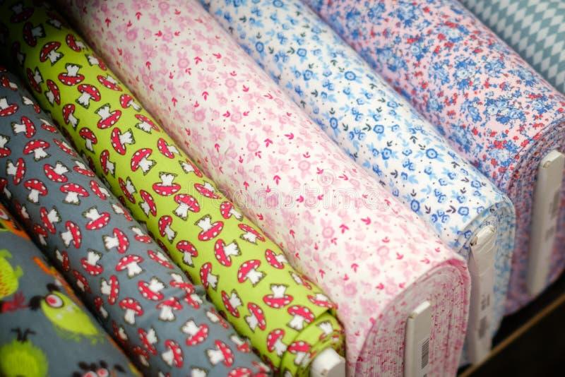 A tela de matéria têxtil rola com teste padrão no mercado fotografia de stock