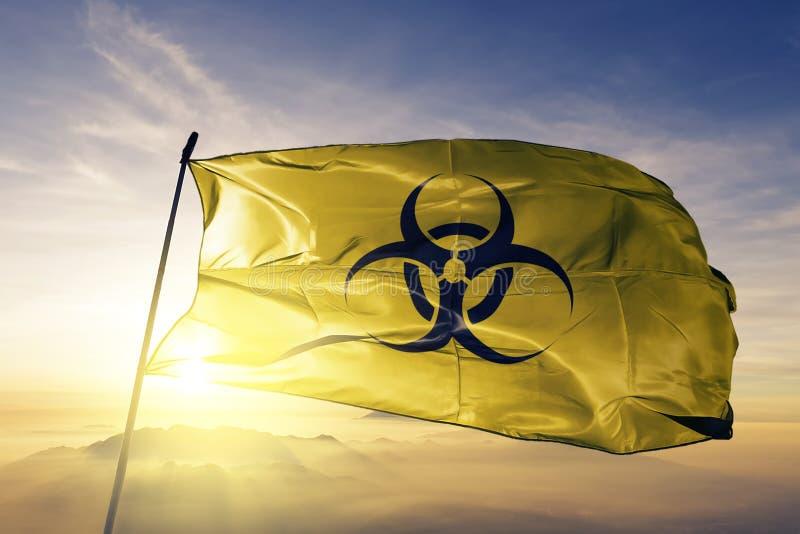 Tela de pano de matéria têxtil da bandeira do Biohazard que acena na névoa superior da névoa do nascer do sol ilustração stock
