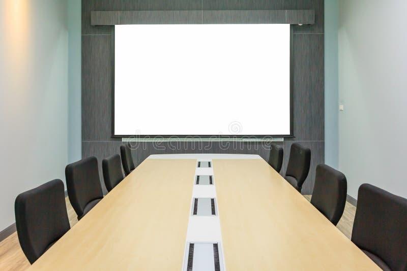 Tela de projeção vazia na sala de reunião com tabela de conferência imagens de stock