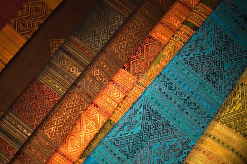 Tela de seda na venda no mercado da noite em Laos imagens de stock