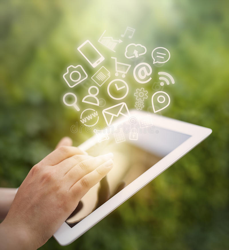 A tela de tablet pc tocante da mão fêmea e os ícones do app voam imagens de stock