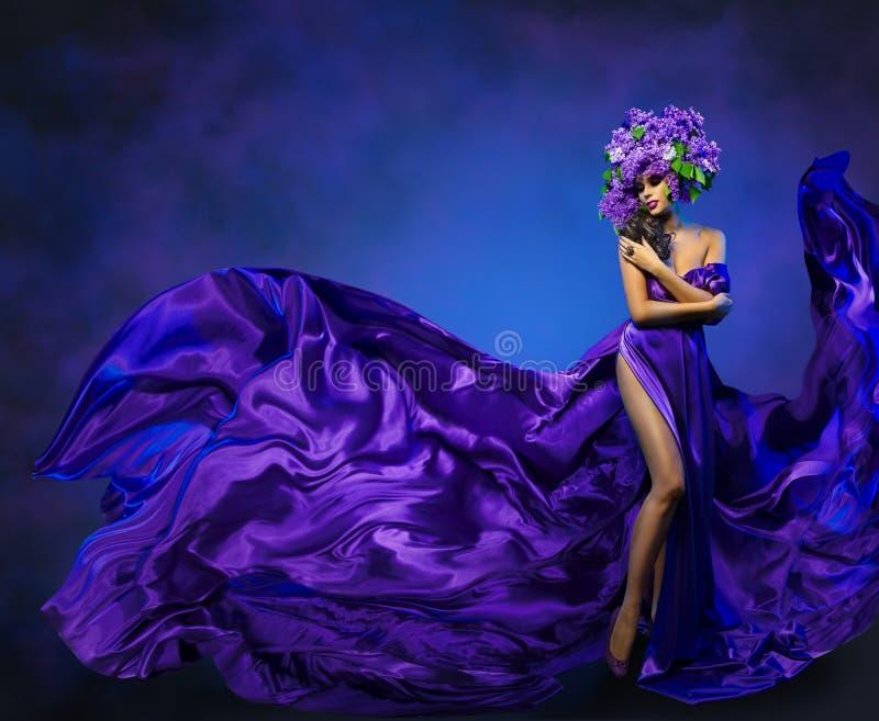 Tela del vuelo del vestido de la flor de la mujer, modelo de moda en sombrero de la lila foto de archivo