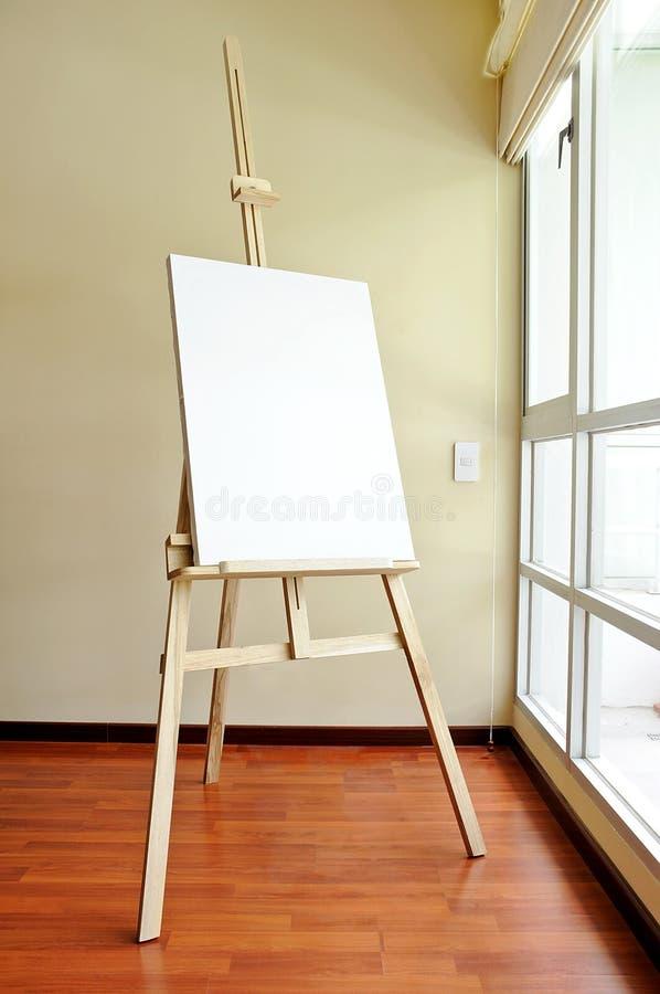 Tela di canapa in bianco su un treppiedi di legno nello studio fotografia stock libera da diritti